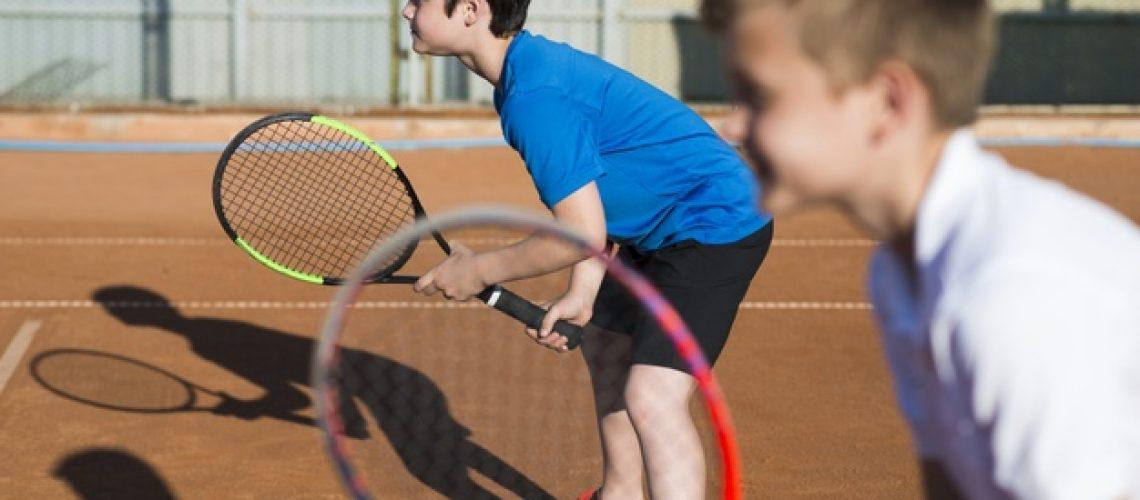 ninos-jugando-al-tenis-dobles_23-2148218636